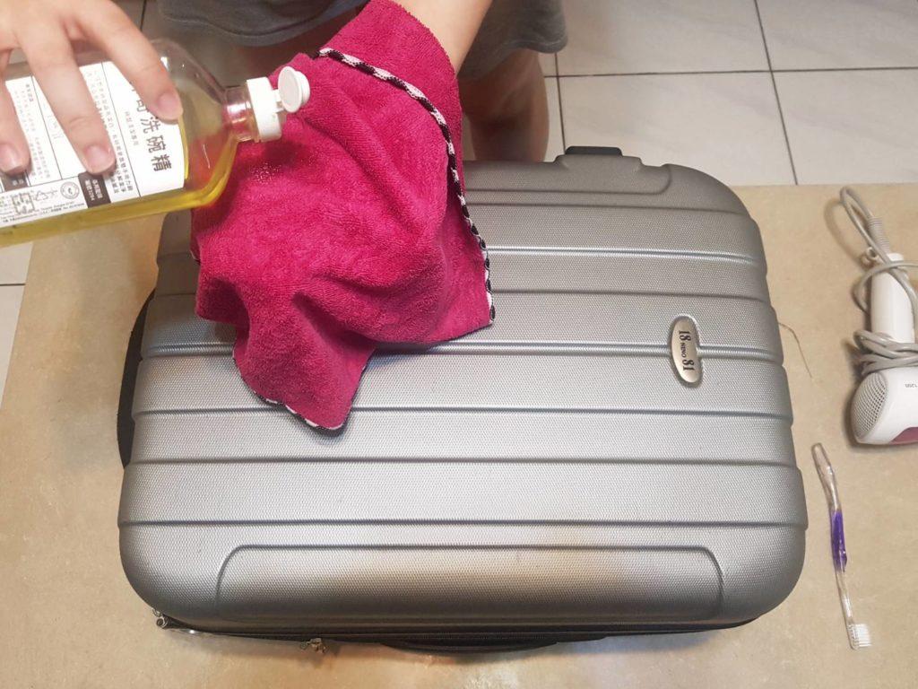 抹布沾稀釋過的洗碗精,擦拭行李箱外殼。